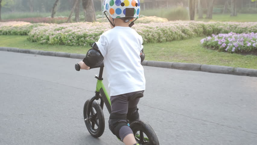 Cute little Asian 2 - 3 years old toddler baby boy child wearing safety helmet learning to ride first balance bike in sunny summer day, kid playing & cycling at park, Cycling with young kids concept | Shutterstock HD Video #1023416053