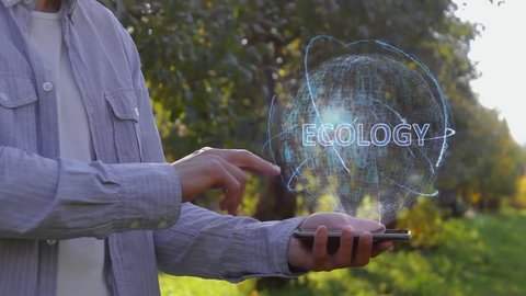 Unrecognizable man shows conceptual hologram with text Ecology. Farmer on the background of the apple orchard in casual clothes with the technology of the future mobile screen