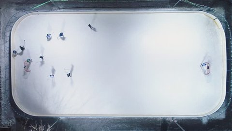 Teams are Playing Ice Hockey on Ice Hockey Rink. Aerial Vertical Top-Down View. Drone Flies Downwards