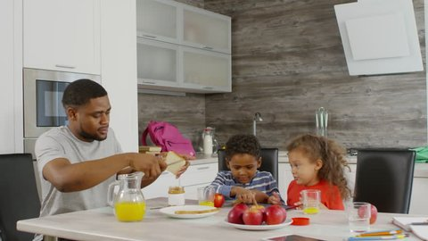 Tracking right of African man spreading peanut butter on toasts and giving them to his children, while they playing games on tablet