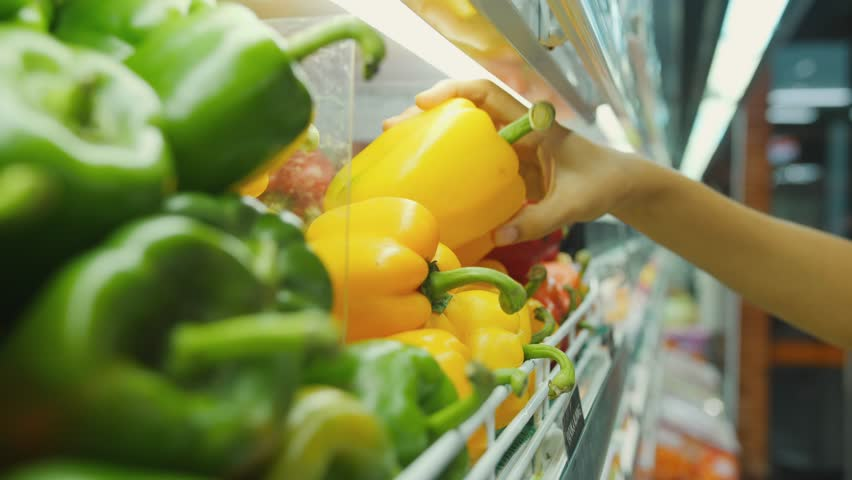 Woman Buying Yellow Pepper in Supermarket. Female Hand Choosing Organic Vegetables in Grocery Store. Zero Waste Shopping and Healthy Lifestyle Concept. 4K Slowmotion. Bali, Indonesia.