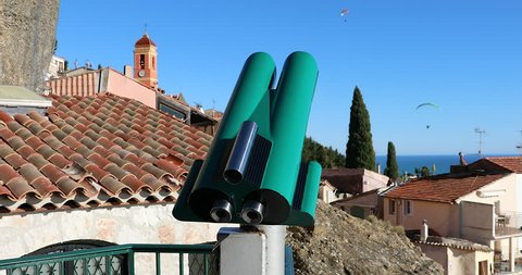 Tourist Coin Operated Binoculars At A Viewpoint In Roquebrune-Cap-Martin, Old French Medieval Village With Paragliding In The Blue Sky, Mediterranean Sea On The French Riviera, France, Europe - DCi 4K