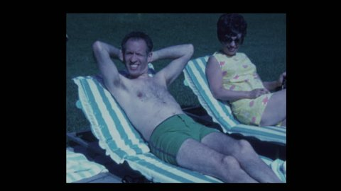 1971 Husband and wife relaxing by hotel pool