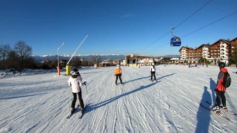 Bansko, Bulgaria - circa Feb, 2018: Crowd of people on ski road just before the sunset in Bansko, Bulgaria. Bansko is a popular winter ski resort where a world ski cup is held. Slow motion cinematic s