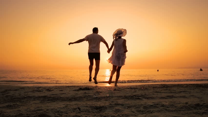 Romantic couple running on beach at sea sunset holding hands and jumping in slow motion. Man takes woman in air and turning her around. Concept of love and happiness | Shutterstock HD Video #1023646453