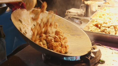 Asian Street food: Chef Cooking Pad Thai in Wok at Night Food Market. 4K Slowmotion. Kuala Lumpur, Malaysia.