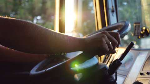 Unrecognizable man holding his hands on steering wheel and driving car at country road on warm summer day. Truck driver rides to destination. View from the lorry cab. Slow motion Close up