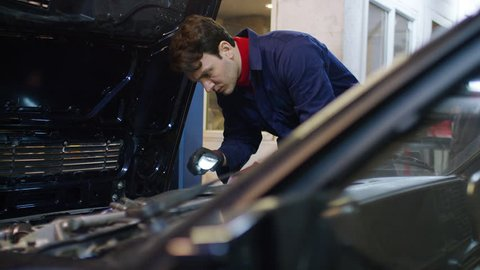 Mechanic inspecting under the bonnet of a car with an LED light