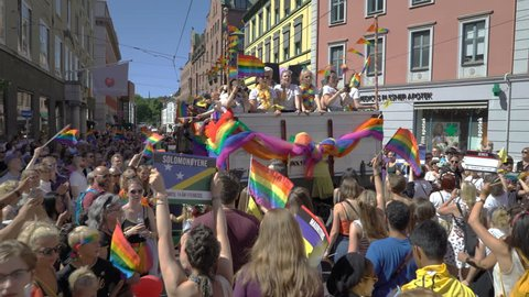 OSLO, NORWAY - JUNE 30, 2018: A lot of fancy-dress people with rainbow flags dance, sing and laugh in the street. The Pride Parade, the highlight of Oslo Pride Week, is a huge, vibrant parade filling
