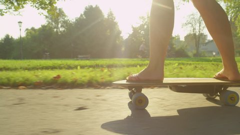SLOW MOTION, LENS FLARE, CLOSE UP: Sporty girl in flip flops skating in the park on a sunny spring day. Unrecognizable young woman casually riding her electric longboard down the scenic asphalt trail.