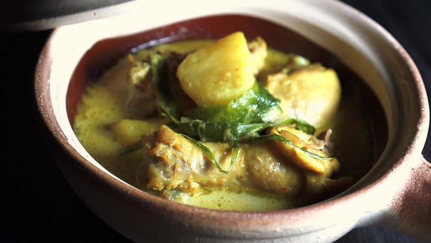 Cinematic Footage. Chicken in thick coconut gravy with turmeric and chilli, known as Masak Lemak Cili Api in Malaysia. | Shutterstock HD Video #1023786133