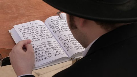Jerusalem, Israel - January 2nd 2019: Orthodox Religious Jew reading The Psalms - Chapter 119 (Bible) at Walls of Jerusalem.