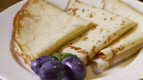 crepe pancakes on a white plate poured red raspberry jam. plums on a plate
