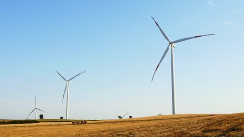 Wind Turbines with a farm tractor on the field. Tractor tilling dusty fields near the base of wind turbines in Thrace, Turkey Country