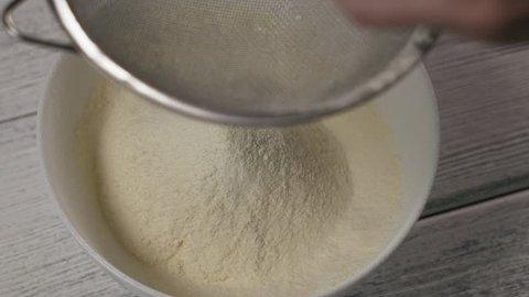 Close-up, Slow Motion, Woman's Hand Flour Flour Through a Sieve in a White Bowl