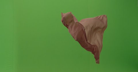 Abstract material floating cloth fabric against green screen in slow motion