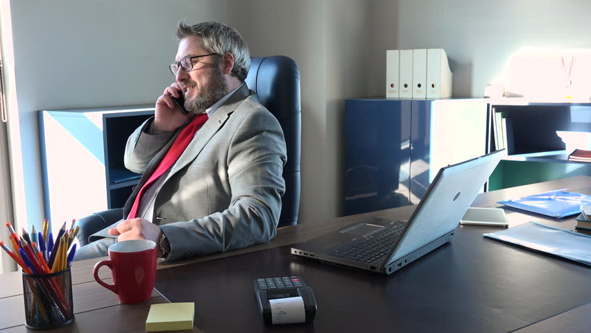 Caucasian manager talking on mobile phone and gets good news. Happy man working in modern office with successful strategy, white smiling businessman at executive workplace, winning business model | Shutterstock HD Video #1023862633