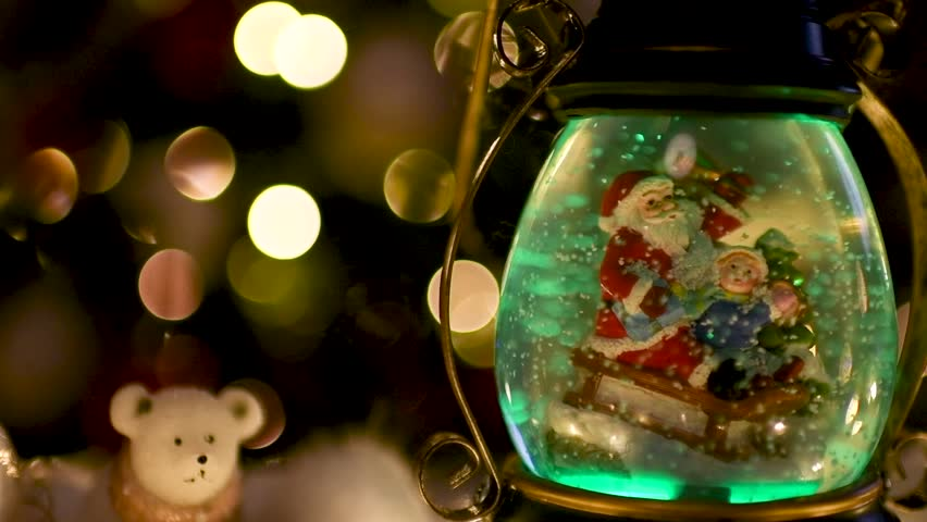 Beautiful Christmas scene with snow globe that changes color and blurred lights in the background. Flat plane