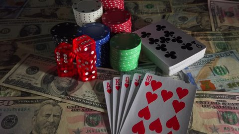 Gambling items with light source moving from right to left and back again casting shadows over US $ Dollar Banknotes, Playing Cards, Poker Chips and Dice