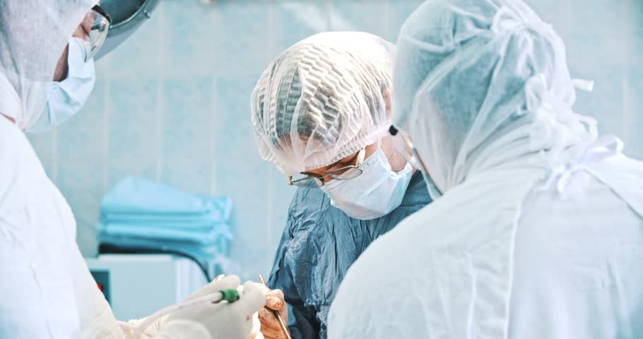 Team of surgeon in uniform perform operation on a patient at cardiac surgery clinic
