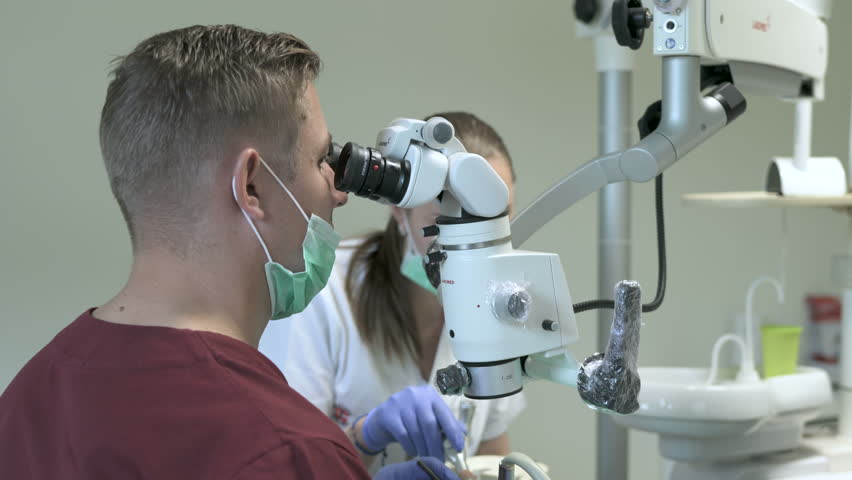Sighetul Marmatiei, Romania - July, 2016: Dentist with assistant treating patient using a microscope in a dental clinic. #1023963713
