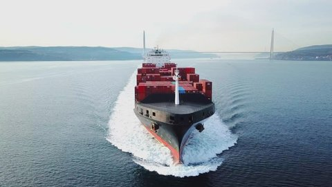 ISTANBUL - FEB 3, 2019: Bow and front deck of container ship on ride. Aerial frontal view as cargo ship ploughs through waters at sea. Half loaded vessel moves at calm water of Bosphorus shipway. Clos