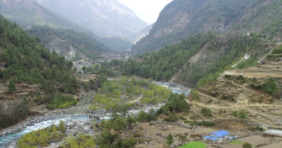 Amazing wide shot POV AERIAL flying through a mountain canyon over a fresh green river flowing through forest in a Nepal Tibet China village town