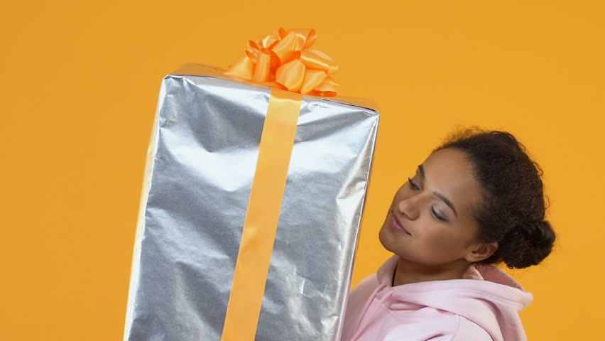 Happy african female holding sizable gift box in hands, holiday package, sale | Shutterstock HD Video #1024022033