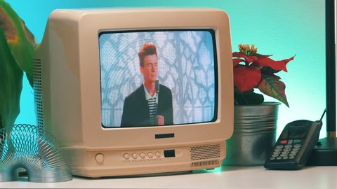 MONTREAL, CANADA - February 2019 : Rick Astley singing the popular Never gonna give you up song playing on TV 80's 90's style. Retro looking desk and setup with old television CRT monitor.
