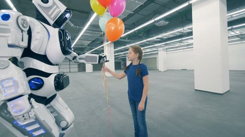 Robot gives balloons and its hand to a girl in a storage unit