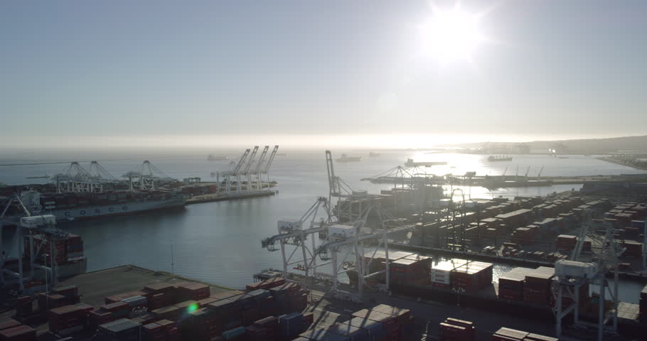 Aerial footage ocean wide shot of cargo container ships from a helicopter view of shipping industry in the port of Los Angeles and Long Beach Harbor in the United States