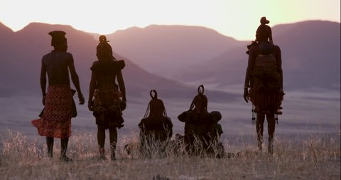 4K view of people from the Himba tribe in traditional dress, watching the sun setting on the mountains, Namib desert, Namibia