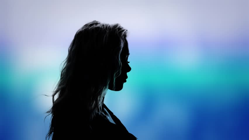 Abstract stylized side view silhouette of a beautiful young woman with her hair blowing in the breeze against a dreamy blue background | Shutterstock HD Video #1024059293