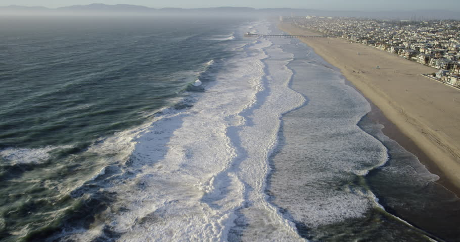 Aerial wide shot POV of California coastline and whitewater waves crashing on the beach from a helicopter view showing the ocean community and pier in Manhattan Beach, Los Angeles, United States