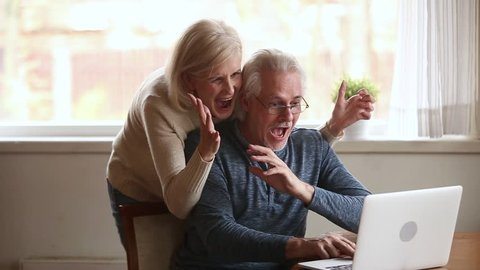 Excited happy senior old family couple winners using laptop overjoyed by unbelievable online betting bid playing internet casino game lottery win screaming with joy looking at computer screen