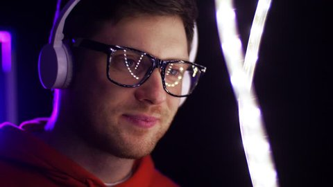 music, leisure and people concept - portrait of young man in wireless headphones and glasses over ultra violet neon lights in dark room of night club