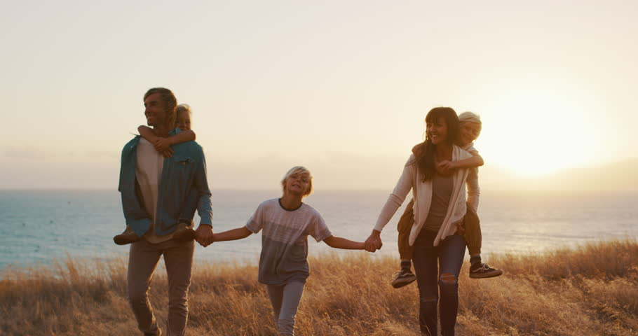 Happy smiling family holding hands walking through golden field at sunset by the ocean, piggy back ride | Shutterstock HD Video #1024117913