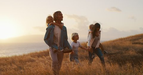 Happy smiling family holding hands walking through golden field at sunset by the ocean, piggy back ride