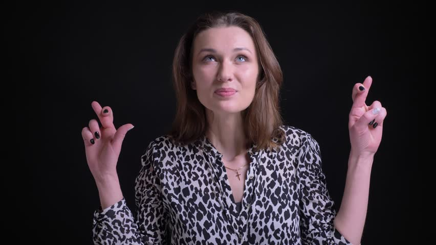 Closeup portrait of adult caucasian female being anxious and having her fingers crossed while looking straight at camera | Shutterstock HD Video #1024149293