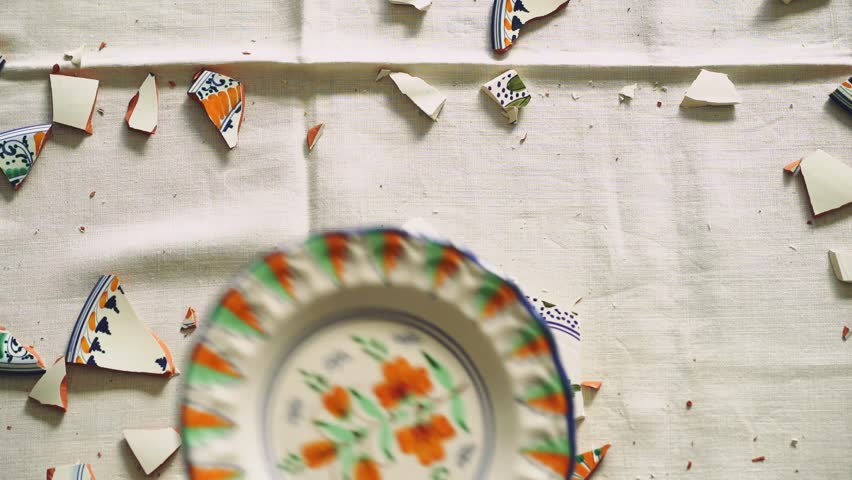Crockery thrown down on table. Wedding-eve party. Broken shards of dishes on tablecloth. Polterabend: Refers a party on the eve of a wedding in Germany, at which crockery is smashed to bring good luck