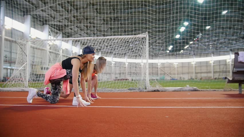 Two young athletic women start running in sports arena | Shutterstock HD Video #1024169183