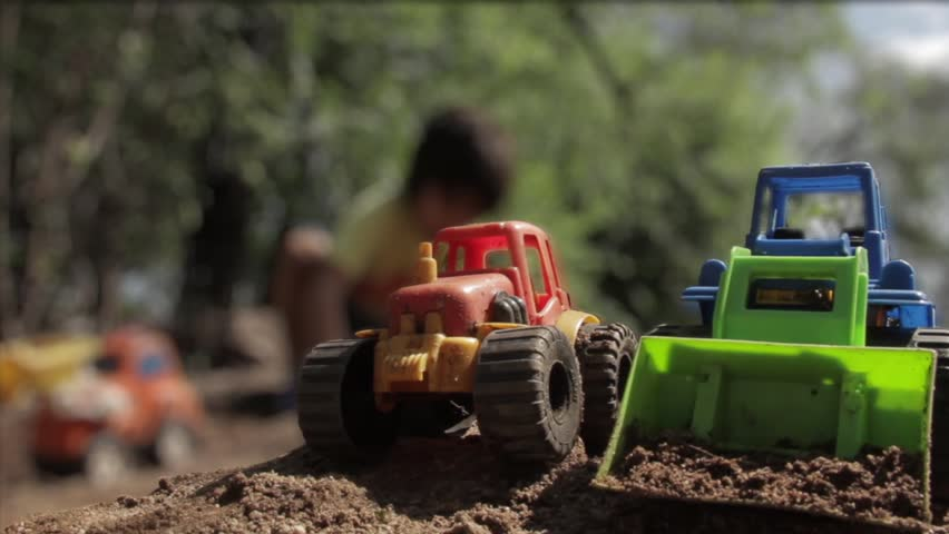 Kid Playing Outside with Toy Tractors. | Shutterstock HD Video #1024171583