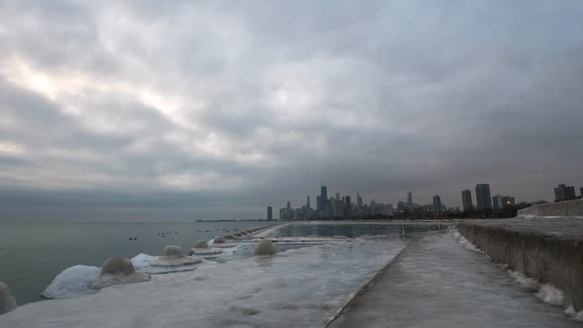 Beautiful panning timelapse along Lake Michigan in Chicago with geese swimming on the pond at sunrise with clouds moving overhead with ice covering the water and shoreline in winter.
