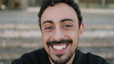 Close up shot of young Arabic mans face with dark curly hair and beard in black hoodie sitting on stairs outside, having video chat with friend, waving hand. Lifestyle, communication concept