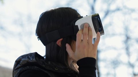 Side view of young dark-haired woman in warm black waistcoat wearing virtual reality glasses in early autumn park, setting up necessary device parameters. High technology, VR concept