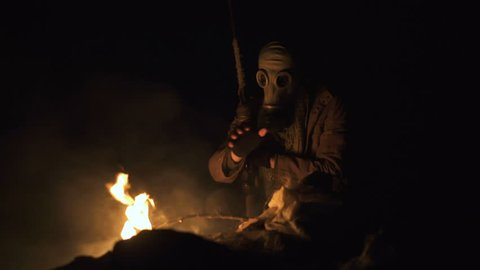 Stalker survivor Soldier wearing Gas Mask in an Apocalypse War scenario Sitting with old-style rifle near the fire