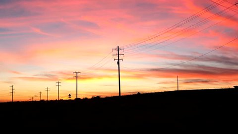 A colorful sunset sky looking down a country road in the USA with telephone poles and electric wires in silhouette vanishing into the distance.