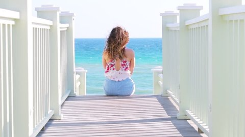 Slow motion of young woman back sitting on wooden boardwalk steps leading to beach with view on ocean in Seaside, Florida, watching waves, standing up and walking away