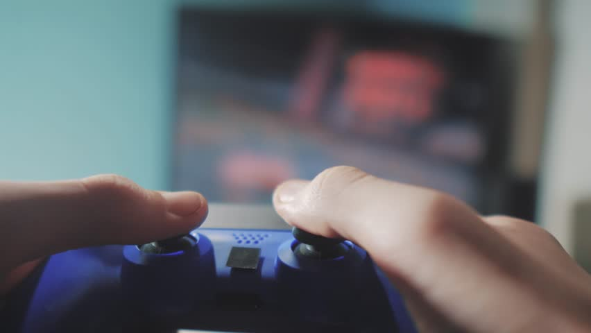 Playing video game console on tv. Hand hold new joystick online video console on tv. Gamer play game with gamepad controller. Gaming man holding simulator joypad. Person with keypad joystick in arms   Shutterstock HD Video #1024279043