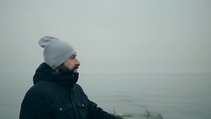 Bearded man in a black jacket and a gray hat on the beach shows off | Shutterstock HD Video #1024290953